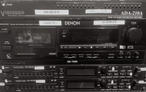 This image shows a stack of equipment with 2 cd player at the bottom, a cassette player above it and an audio distribution amp on top