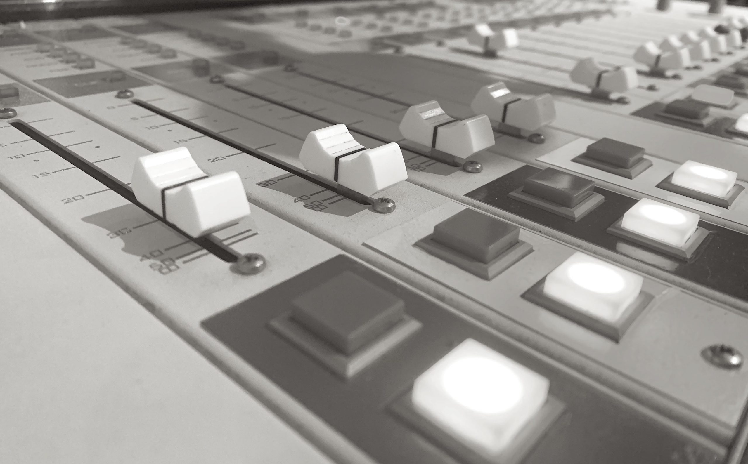 This image shows a close up of the fader and control buttons of the broadcast board at Vancouver Co-op Radio CFRO 100.5 FM