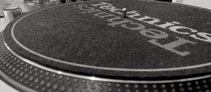 This image shows a close up of a Technic 1200 turntable and a Pioneer DJ mixer