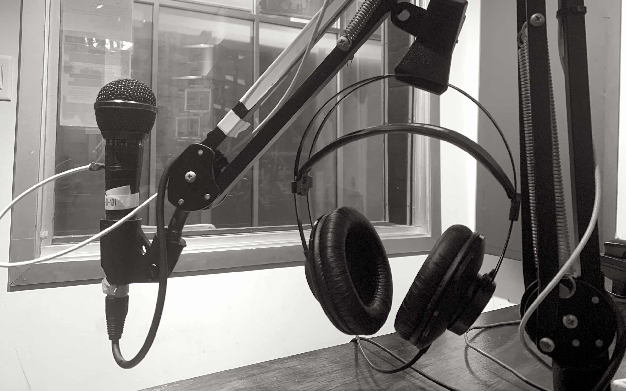 This image shows a close up of a microphone and headphones on a boom arm stand above a wooden desk, with a window in the background