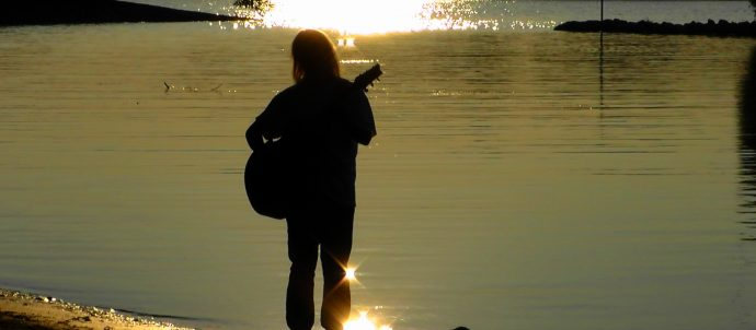 person with guitar in front of river